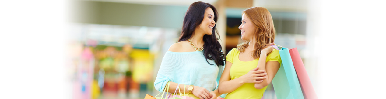 Two happy woman in mall holding shopping bags Los Angeles CA