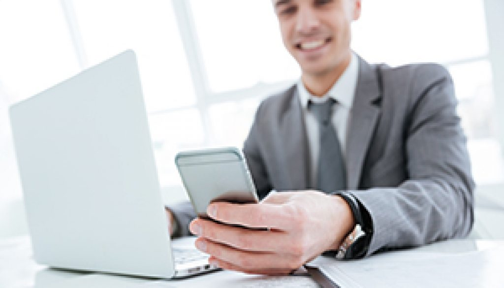 Business man sitting by the table with laptop and phone